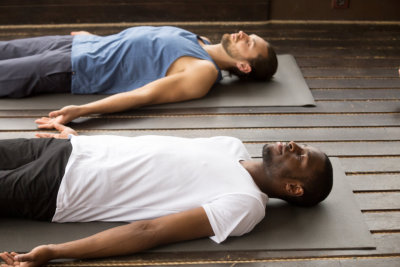 Group of two young afro american and caucasian sporty people practicing yoga lesson lying in Dead Body or Corpse pose