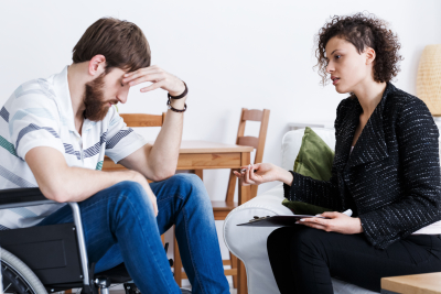 woman counseling a sad man in a wheelchair